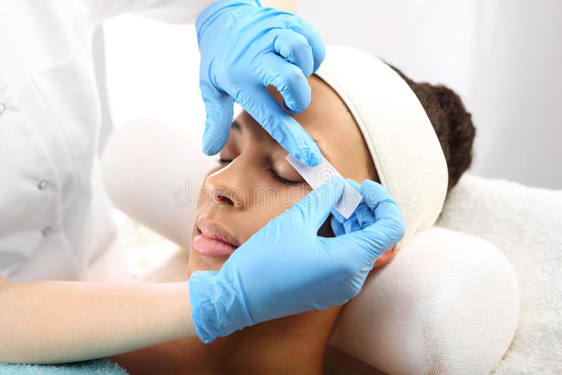 Styling eyebrows in the beauty salon. Hair removal, eyebrow regulation wax in the beauty salon royalty free stock image