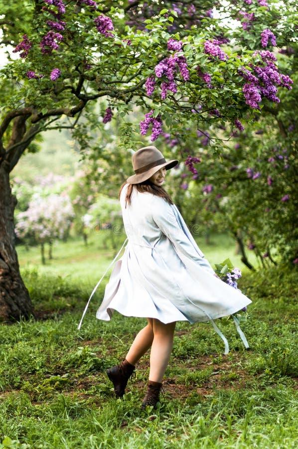 Stylis愉快的女孩跳舞在淡紫色庭院里 库存照片