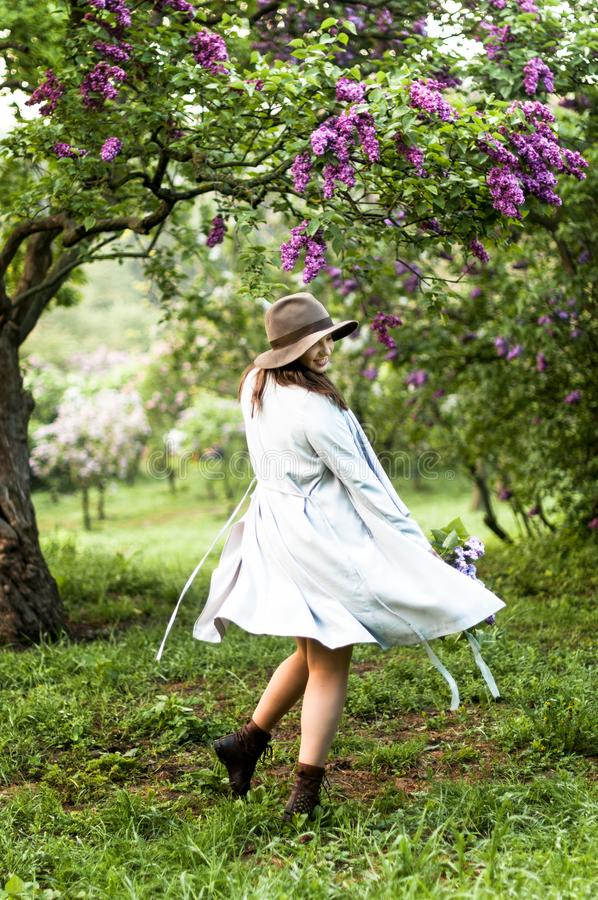 Stylis dziewczyny szczęśliwy taniec w lilym ogródzie zdjęcia stock