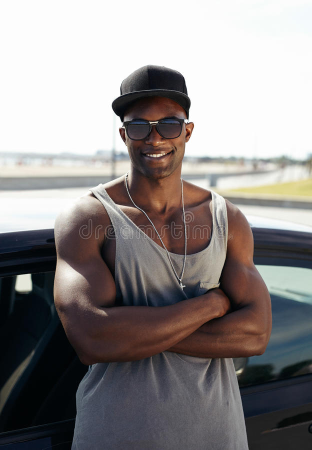 Stylised young muscular man leaning against car. Portrait of handsome african guy with his arms crossed leaning against a car smiling. Stylised muscular guy stock photos