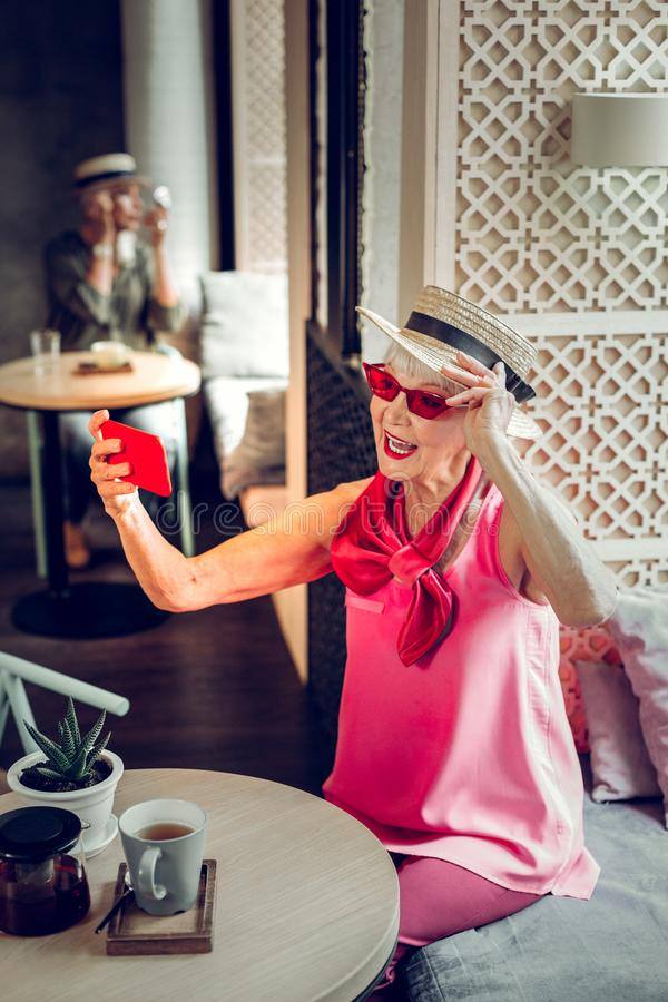 Delighted aged woman wearing a stylish hat stock photography