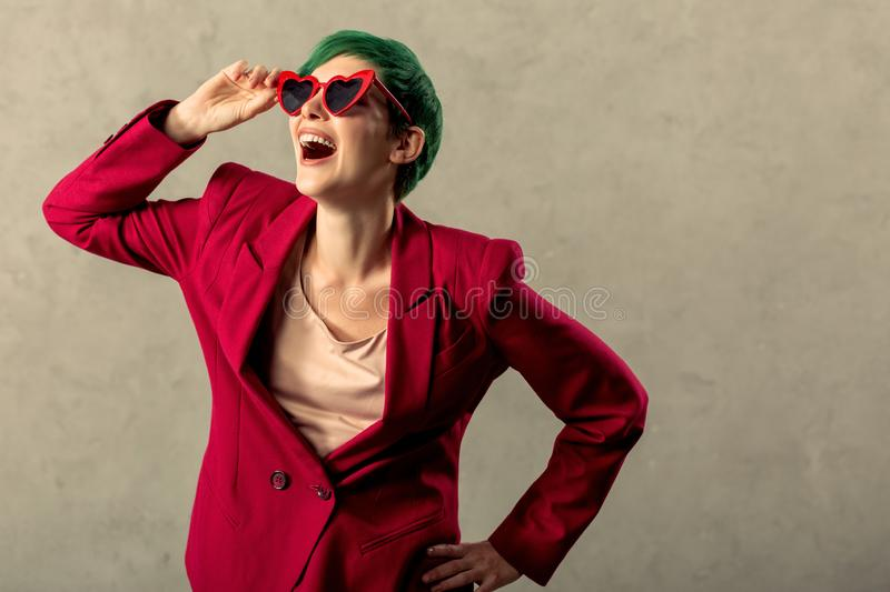 Delighted cheerful young woman touching her sunglasses royalty free stock photos