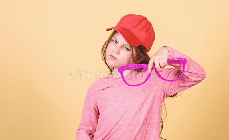 Stylish accessory. Feeling confident with accessories. Girl cute child wear cap or snapback hat hold eyeglasses beige. Background. Little girl wearing bright stock photos