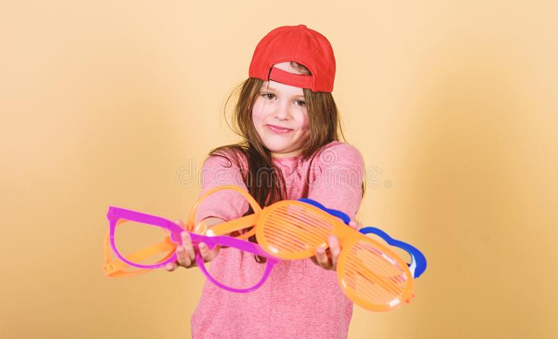 Stylish accessory. Feeling confident with accessories. Girl cute child wear cap or snapback hat hold eyeglasses beige. Background. Modern fashion. Little girl stock image