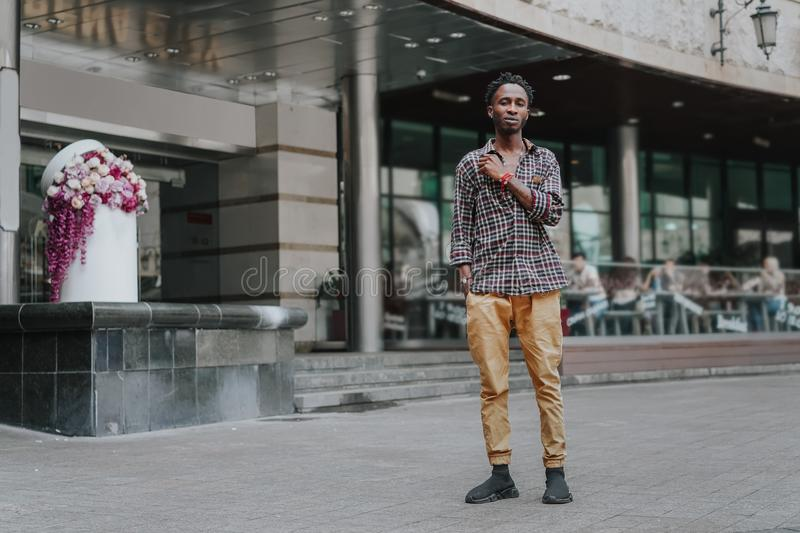Stylish african american boy on the plaid shirt. Trendy hipster and rapper posed at street. Fashionable black guy. A student walks. Stylish african american boy royalty free stock image