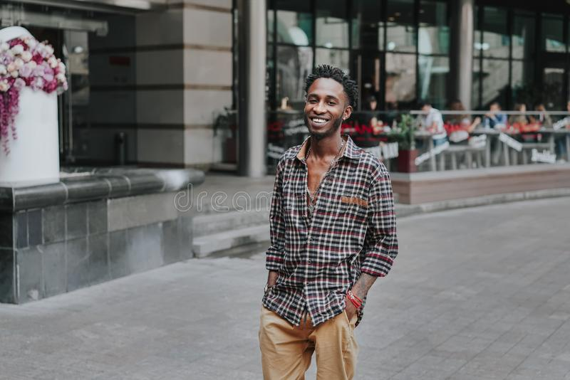 Stylish african american boy on the plaid shirt. Trendy hipster and rapper posed at street. Fashionable black guy. A student walks stock image
