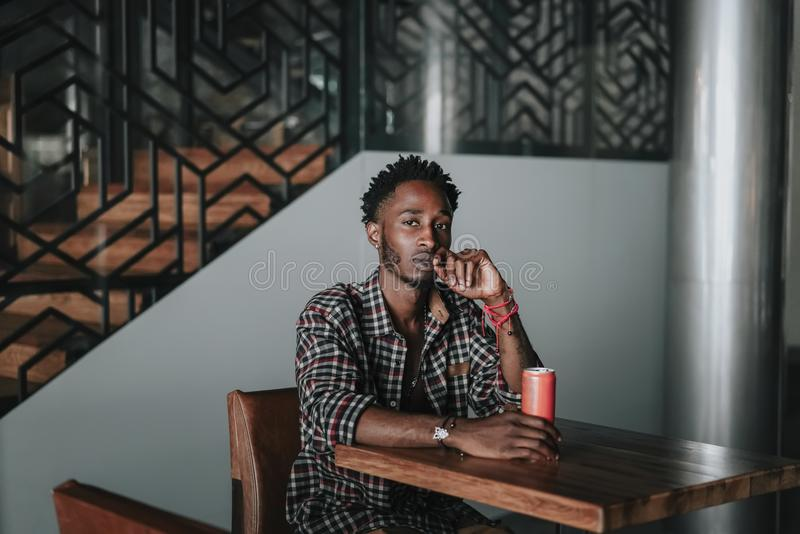 Stylish african american boy on the plaid shirt. Trendy hipster and rapper posed at street sitting on table wooden cafe with a can. Stylish african american boy stock photography