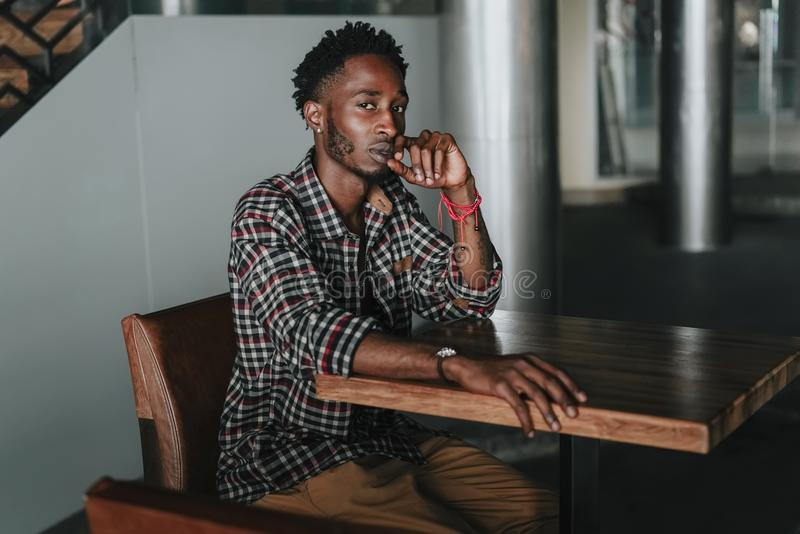 Stylish african american boy on the plaid shirt. Trendy hipster and rapper posed at street sitting on table wooden cafe. Fashionab. Stylish african american boy stock image