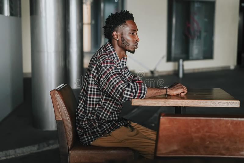 Stylish african american boy on the plaid shirt. Trendy hipster and rapper posed at street sitting on table wooden cafe. Fashionab. Stylish african american boy royalty free stock images