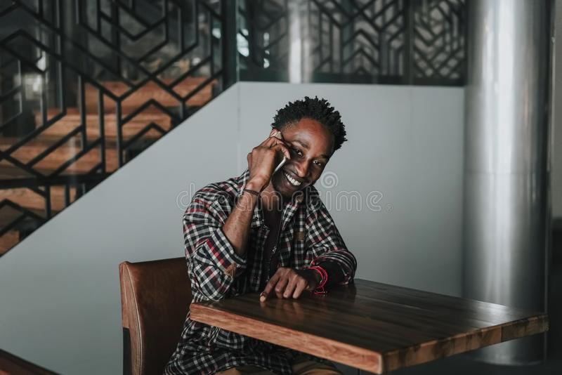 Stylish african american boy on the plaid shirt. Trendy hipster and rapper posed at street sitting on table wooden cafe with mobil royalty free stock photo