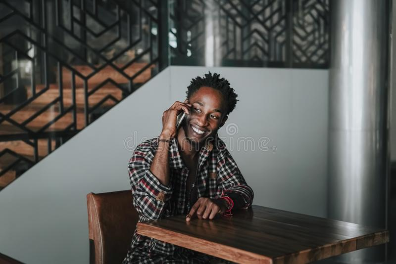 Stylish african american boy on the plaid shirt. Trendy hipster and rapper posed at street sitting on table wooden cafe with mobil. E phone. Fashionable black royalty free stock image