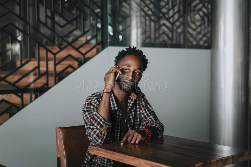 Stylish african american boy on the plaid shirt. Trendy hipster and rapper posed at street sitting on table wooden cafe with mobil. E phone. Fashionable black royalty free stock images