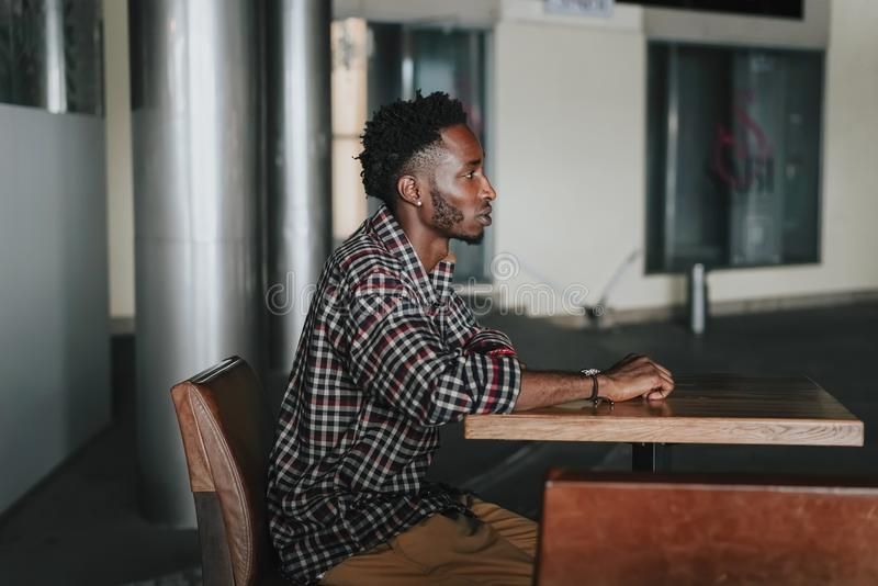 Stylish african american boy on the plaid shirt. Trendy hipster and rapper posed at street sitting on table wooden cafe. Fashionab. Stylish african american boy stock photography