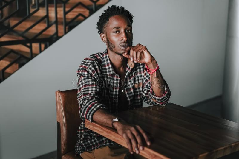 Stylish african american boy on the plaid shirt. Trendy hipster and rapper posed at street sitting on table wooden cafe with mobil. Stylish african american boy royalty free stock photo