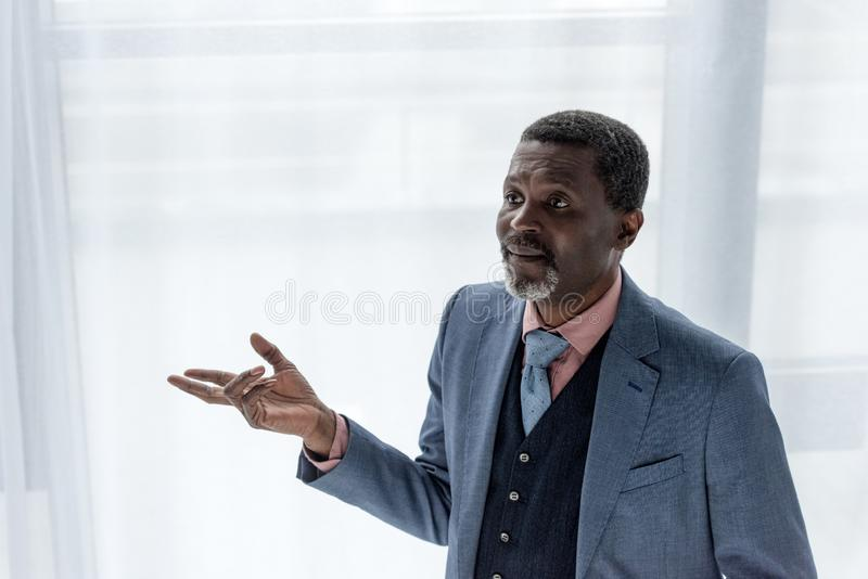 Stylish african american businessman in blue jacket gesturing. Near window royalty free stock images