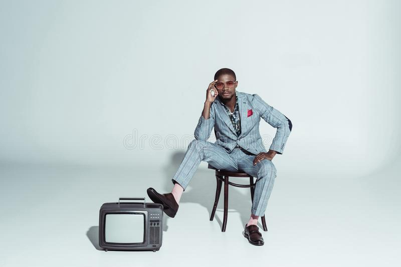 Stylish african american man posing on wooden chair with one leg on a royalty free stock photography