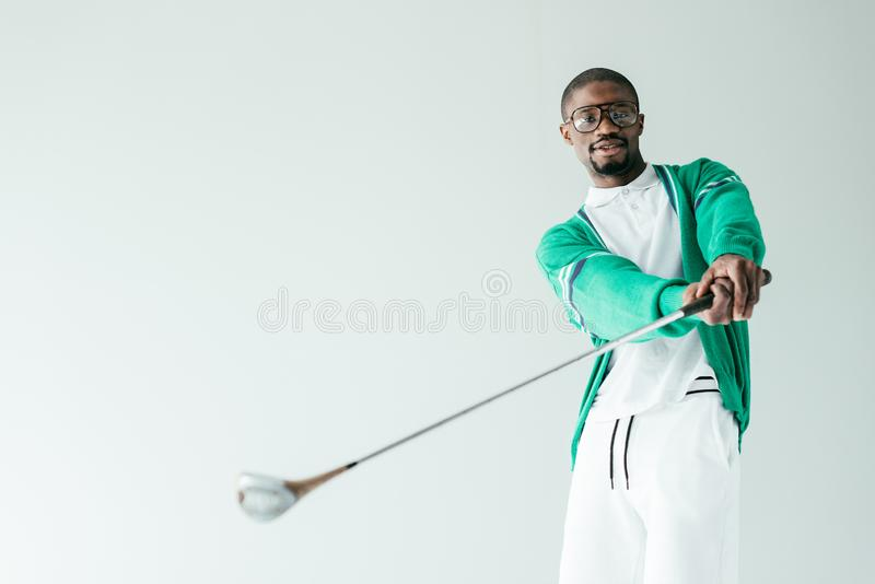 stylish african american man in retro sportswear playing golf royalty free stock photography