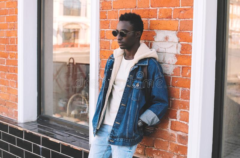 Stylish african man wearing jeans jacket, backpack posing on city street, brick wall. Background stock images