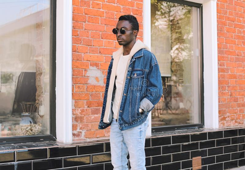 Stylish african man wearing jeans jacket walking on city street over brick wall. Background stock photos