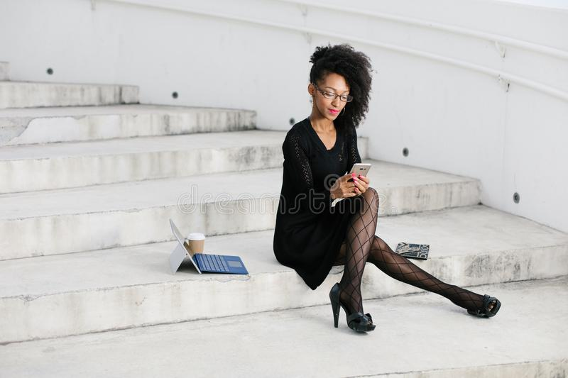 Stylish young afro hair professional woman texting on mobile phone royalty free stock images