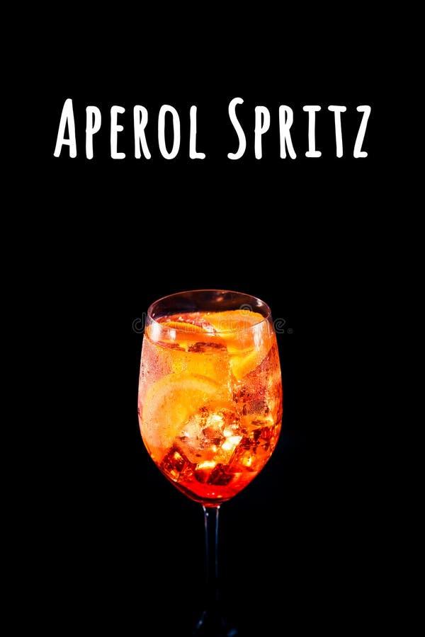 Stylish alcoholic aperol spritz cocktail with orange slice on black background.. Aperol Spritz wording. Stylish alcoholic aperol spritz trendy cocktail with royalty free stock image
