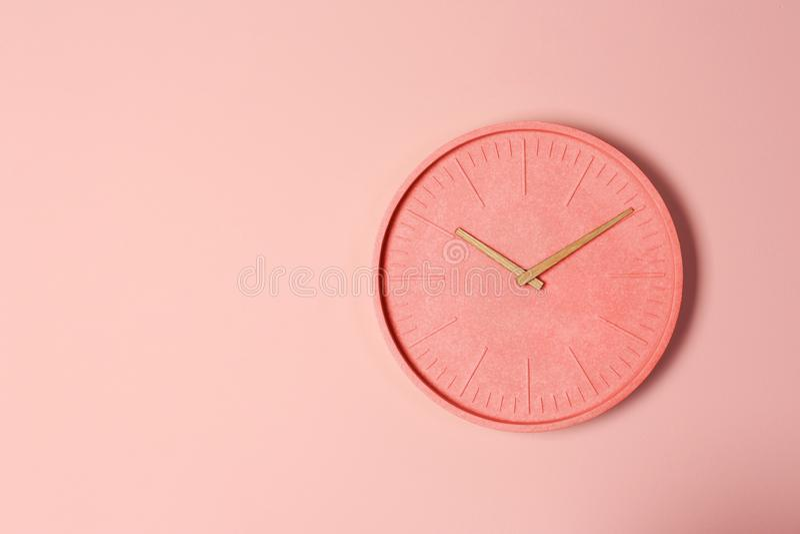 Stylish analog clock hanging on color wall. stock image