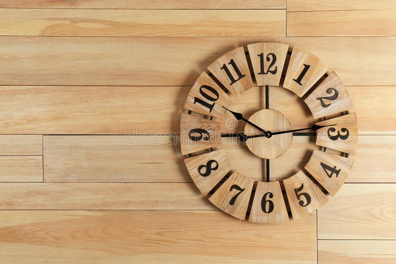 Stylish analog clock hanging on wooden wall stock images