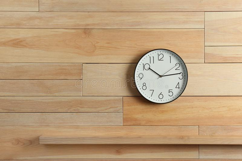 Stylish analog clock hanging on wooden wall royalty free stock image