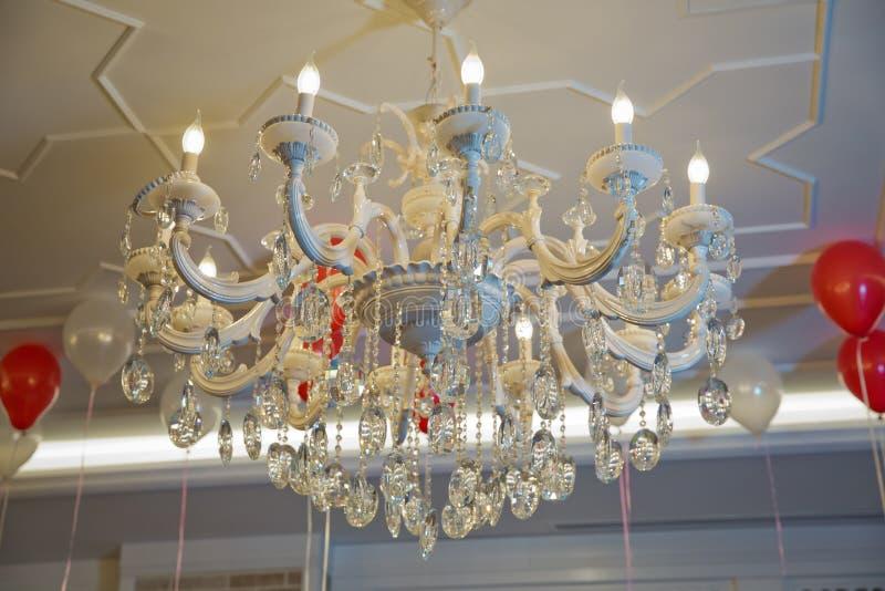 Stylish antique chandelier lit in violet light. beautiful crystal chandelier for decoration . Pink background. Horizontally framed shot . Stylish antique stock images