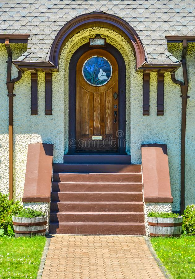 Stylish arch exterior door, wooden door of a house with mosaic glass sections. Elegant front door: arch stylish exterior door, wooden door of a house with stock photography