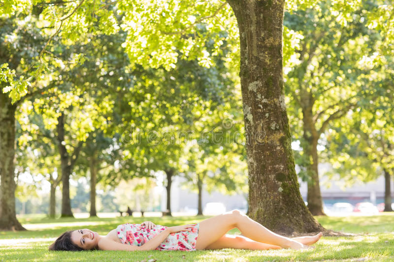Stylish attractive brunette lying on a lawn royalty free stock photos