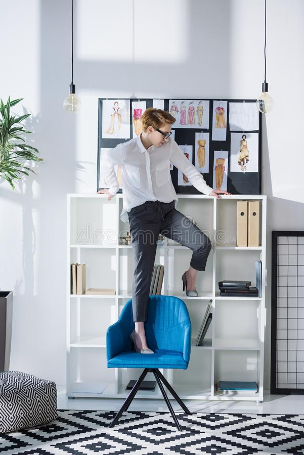 Stylish attractive fashion designer standing on chair. At office royalty free stock photos