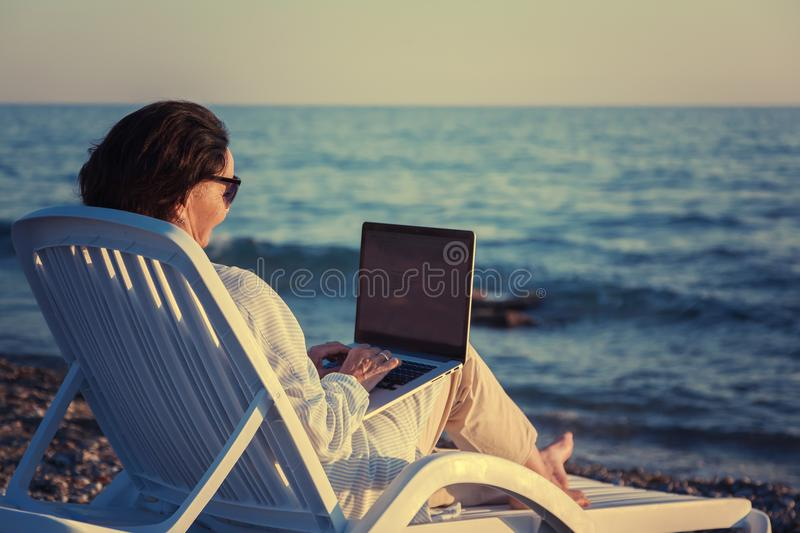 Stylish attractive mature woman 50-60 makes use of laptop on the royalty free stock images