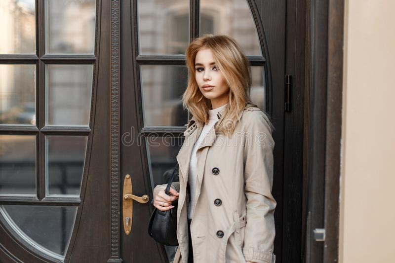 Stylish attractive young blond woman in an autumn coat with a black leather stylish bag stands near a vintage wooden mirror door. stock image