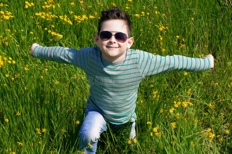 Stylish baby boy with dark hair in striped polo-neck and in tre. Ndy sunglasses. Smile. Sunny weather. Outdoor shot stock photos