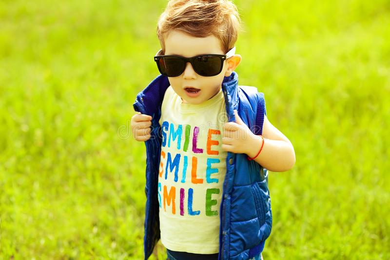 Stylish baby boy with ginger red hair in trendy sunglasses. And blue jacket standing in the park. Hipster style. Sunny weather. SMILE word printed on t-shirt royalty free stock image