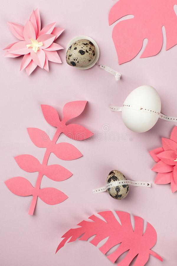 Stylish background with quail and white easter eggs and origami paper flowers on pink background. Flat lay, top view. Easter royalty free stock photos