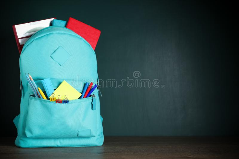 Stylish backpack with school stationery on table against chalkboard. Space for text. Stylish backpack with different school stationery on table against royalty free stock photography