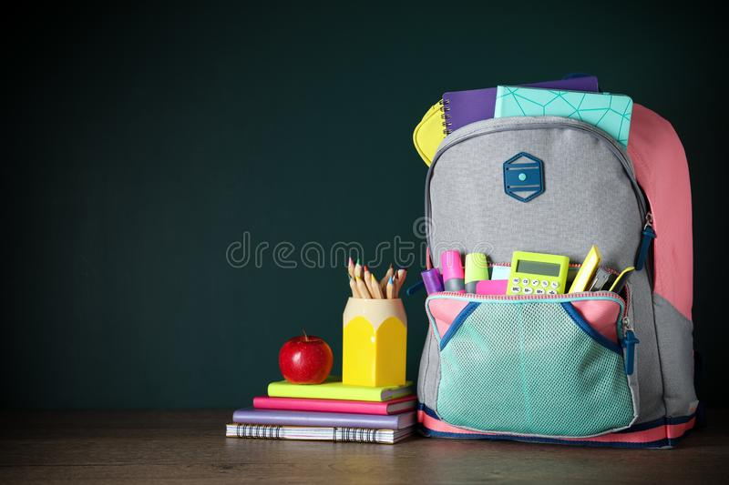 Stylish backpack with different school stationery on table against chalkboard. Space for text. Stylish backpack with different school stationery on table against stock photo