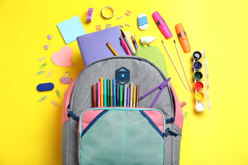 Stylish backpack with different school stationery on yellow. Background, flat lay royalty free stock photography