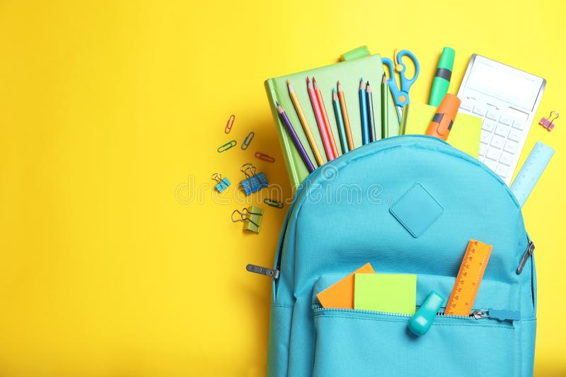 Stylish backpack with different school stationery on yellow, flat lay. Stylish backpack with different school stationery on yellow background, flat lay stock photo