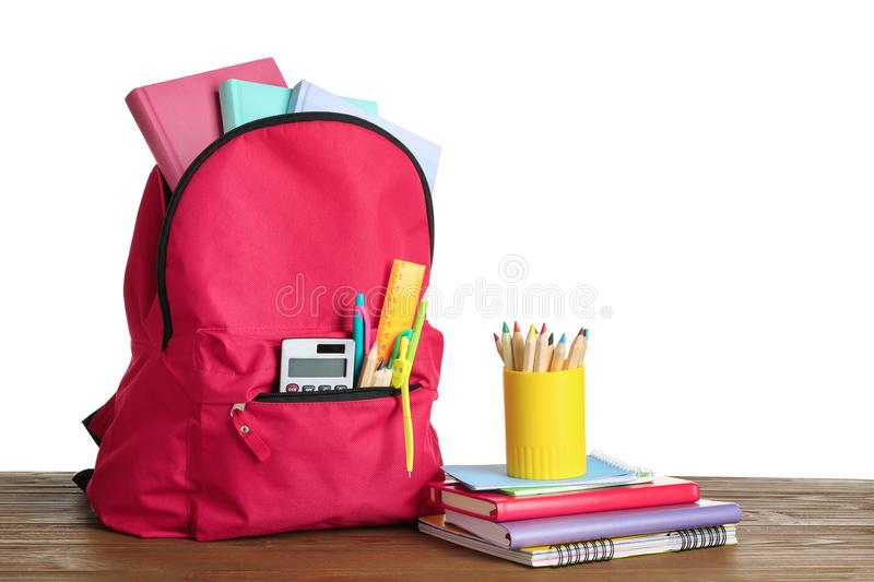 Stylish backpack with school stationery. On table against white background royalty free stock photography