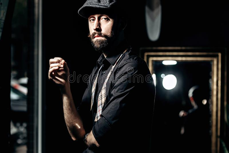 Stylish barber with mustache and beard dressed in a black shirt with untied bow tie and flat cap stands in the dark room royalty free stock photo
