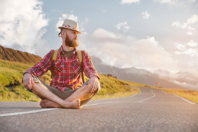 Stylish barefoot bearded male hitchhiker traveler in a hat and with a backpack sits on a suburban asphalt road in the royalty free stock photo