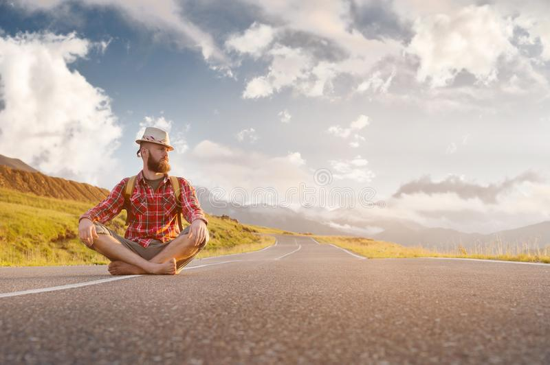 Stylish barefoot bearded male hitchhiker traveler in a hat and with a backpack sits on a suburban asphalt road in the stock photos