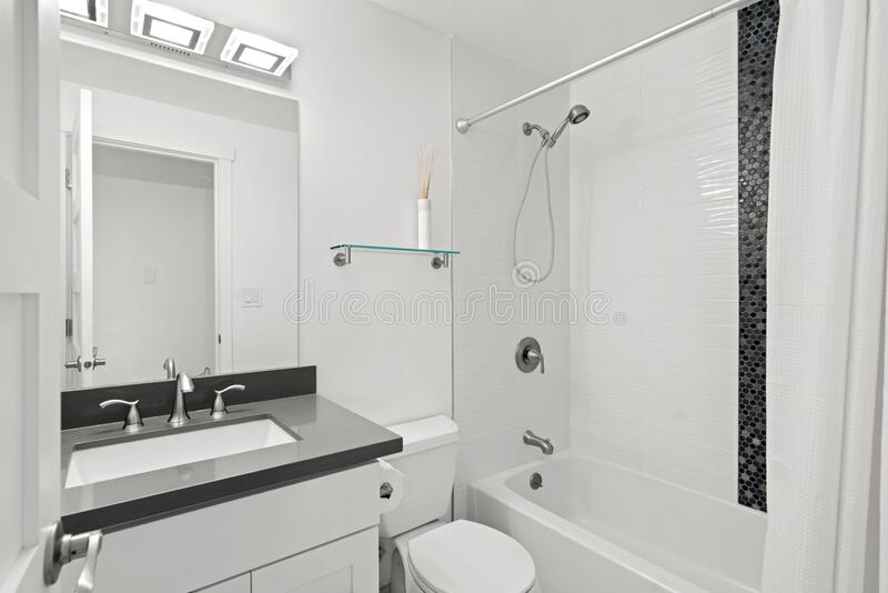 Stylish bathroom interior with dark grey countertop fitted with white porcelain sink. Interior of bathroom with dark grey countertop, white porcelain sink and royalty free stock photo