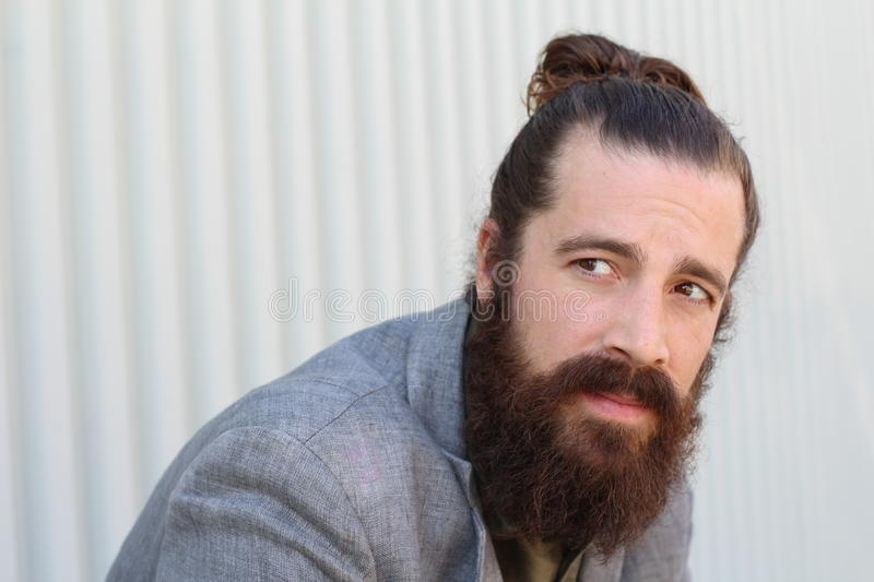Stylish bearded hipster model with man bun hairstyle, lifestyle in the street, depth of field. Copy space on the left side of the royalty free stock image