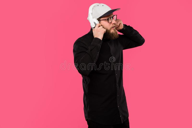 Stylish bearded male hipster wearing eyeglasses and cap hat listening music in headphones isolated. On pink royalty free stock photos