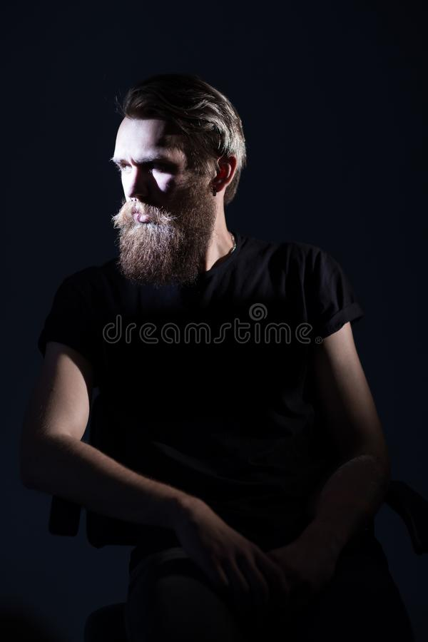 Stylish bearded man in a black t-shirt sitting in a chair royalty free stock image