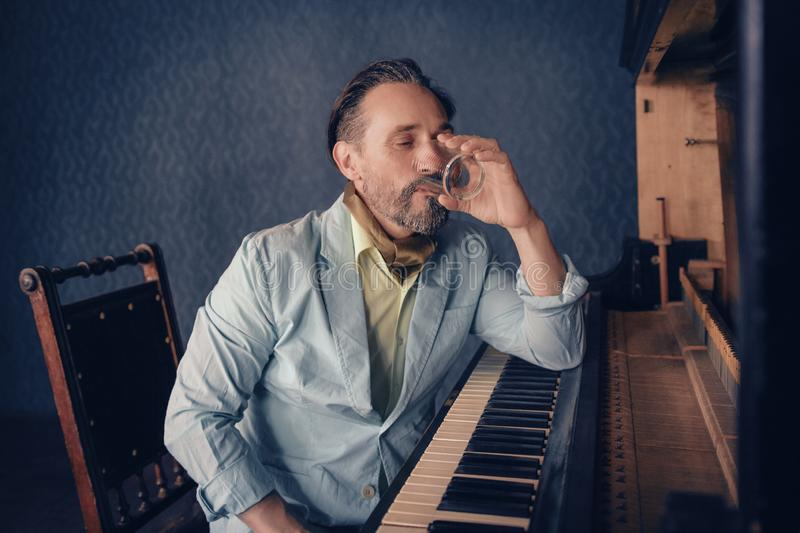Handsome musician composes music sitting at piano royalty free stock image